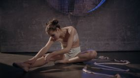 Όμορφη νέα gymnast τοποθέτηση γυναικών με την ταινία γυμναστικής φιλμ μικρού μήκους