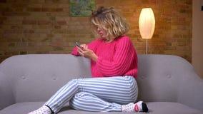 Όμορφη νοικοκυρά στη ρόδινη συνεδρίαση πουλόβερ στο σχεδιάγραμμα στον καναπέ με το χέρι κυμάτων smartphone στη κάμερα στην εγχώρι απόθεμα βίντεο