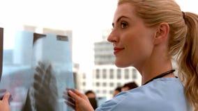 Όμορφη νοσοκόμα που εξετάζει την ακτίνα X φιλμ μικρού μήκους