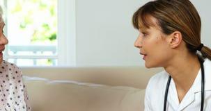 Όμορφη νοσοκόμα που κάνει τον έλεγχο υγείας επάνω με μια ώριμη γυναίκα απόθεμα βίντεο