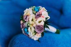 Όμορφη νυφική ανθοδέσμη σε μια μπλε armrest λεωφορείων γαμήλια έννοια Στοκ Φωτογραφίες