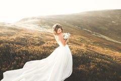 Όμορφη νύφη με μια ανθοδέσμη στο υπόβαθρο βουνών στο ηλιοβασίλεμα Στοκ Φωτογραφίες