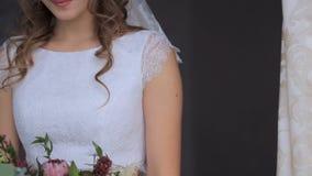 Όμορφη νύφη με μια ανθοδέσμη των λουλουδιών σε ένα σκοτεινό υπόβαθρο φιλμ μικρού μήκους