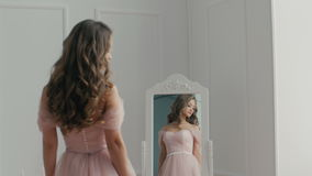 Όμορφη νύφη με την ανθοδέσμη κοντά στον καθρέφτη απόθεμα βίντεο
