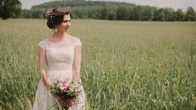 Όμορφη νύφη που στέκεται σε έναν τομέα σίτου σε ένα αρκετά άσπρο φόρεμα, που κρατά μια θαυμάσια ανθοδέσμη στα χέρια της ευτυχής ε απόθεμα βίντεο