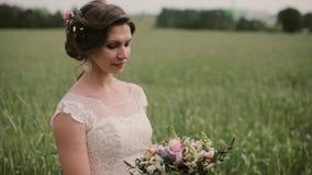 Όμορφη νύφη που στέκεται σε έναν τομέα σίτου σε ένα αρκετά άσπρο φόρεμα, που εξετάζει μια ανθοδέσμη στα χέρια της ευτυχής εκλεκτή φιλμ μικρού μήκους