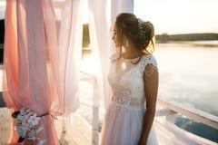 Όμορφη νύφη που στέκεται στο ηλιοβασίλεμα Στοκ εικόνες με δικαίωμα ελεύθερης χρήσης