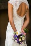 Όμορφη νύφη σε ένα άσπρο φόρεμα με μια ανθοδέσμη των λουλουδιών Στοκ Εικόνα
