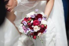Όμορφη νύφη στην άσπρη κινηματογράφηση σε πρώτο πλάνο γαμήλιων ανθοδεσμών εκμετάλλευσης φορεμάτων Στοκ Εικόνες
