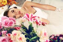 Όμορφη νύφη στην κομψή τοποθέτηση γαμήλιων φορεμάτων μεταξύ των λουλουδιών Στοκ Φωτογραφίες