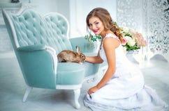 Όμορφη νύφη στο γαμήλιο φόρεμα με ένα κουνέλι σε ετοιμότητα του Στοκ Εικόνες