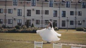 Όμορφη νύφη brunette που μένει εξωτερική και που γυρίζει γύρω Η γυναίκα στο άσπρο γαμήλιο φόρεμα απολαμβάνει την ημέρα της τελετή απόθεμα βίντεο
