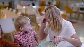 Όμορφη ξανθή αγαπώντας μητέρα με το γιο και την κόρη που στον άνετο καφέ τα σαββατοκύριακα φιλμ μικρού μήκους