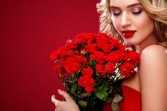 Όμορφη ξανθή ανθοδέσμη εκμετάλλευσης γυναικών των κόκκινων τριαντάφυλλων Βαλεντίνος Αγίου και διεθνής ημέρα γυναικών ` s, οκτώ Μα στοκ φωτογραφίες