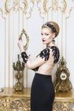 Όμορφη ξανθή βασιλική γυναίκα που βάζει σε έναν αναδρομικό καναπέ στο πανέμορφο φόρεμα πολυτέλειας Στοκ Εικόνες