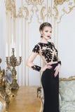 Όμορφη ξανθή βασιλική γυναίκα που στέκεται κοντά στον αναδρομικό πίνακα στο πανέμορφο φόρεμα πολυτέλειας με το ποτήρι του κρασιού Στοκ εικόνα με δικαίωμα ελεύθερης χρήσης