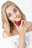 Όμορφη ξανθή γυναίκα με την ευχαρίστηση που τρώει το νεκταρίνι στοκ εικόνα
