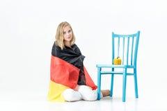 Όμορφη ξανθή γυναίκα με τη σημαία της Γερμανίας και των λαχανικών Εξαγωγή και εισαγωγή των λαχανικών Στοκ Εικόνες