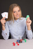 Όμορφη ξανθή γυναίκα με τις κάρτες παιχνιδιού και τα τσιπ πόκερ άνω της GR Στοκ Εικόνες