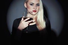 Όμορφη ξανθή γυναίκα με το κόκκινο κρασί πίνοντας κορίτσι Στοκ Φωτογραφία