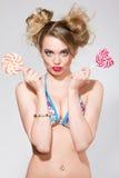 Όμορφη ξανθή γυναίκα με το φωτεινό makeup γοητείας στο μαγιό που κρατά καρδιά 2 τη ρόδινη lollipops Στοκ εικόνα με δικαίωμα ελεύθερης χρήσης