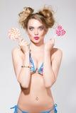 Όμορφη ξανθή γυναίκα με το φωτεινό makeup γοητείας στο μαγιό που κρατά καρδιά 2 τη ρόδινη lollipops Στοκ Εικόνες