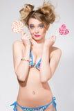 Όμορφη ξανθή γυναίκα με το φωτεινό makeup γοητείας στο μαγιό που κρατά καρδιά 2 τη ρόδινη lollipops Στοκ εικόνες με δικαίωμα ελεύθερης χρήσης