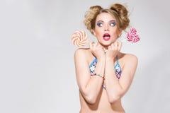 Όμορφη ξανθή γυναίκα με το φωτεινό makeup γοητείας στο μαγιό που κρατά καρδιά 2 τη ρόδινη lollipops Στοκ Εικόνα