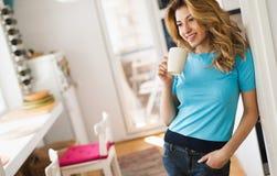 Όμορφη ξανθή γυναίκα που έχει τον καφέ πρωινού στο σπίτι Στοκ φωτογραφία με δικαίωμα ελεύθερης χρήσης