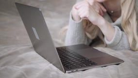 Όμορφη ξανθή γυναίκα που βρίσκεται στο κρεβάτι με το γκρίζο lap-top αργιλίου Χαμόγελα κοριτσιών, καλή διάθεση Blogging, κοιτάζοντ απόθεμα βίντεο