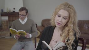 Όμορφη ξανθή γυναίκα που διαβάζει το βιβλίο στο πρώτο πλάνο ενώ συγκρατημένα ντυμένος άνδρας που μελετά το υλικό στο υπόβαθρο φιλμ μικρού μήκους