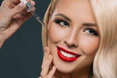 όμορφη ξανθή γυναίκα που εφαρμόζει τον ορό στο πρόσωπό της, στοκ εικόνα