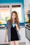 Όμορφη ξανθή γυναίκα που πίνει coffe ή τσάι από το φλυτζάνι Στοκ Εικόνες