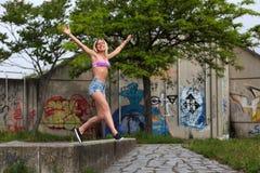 Όμορφη ξανθή γυναίκα που πηδά και που χαμογελά στοκ εικόνες
