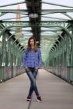 Όμορφη ξανθή γυναίκα που στέκεται σε μια γέφυρα με τα γκράφιτι στοκ εικόνες