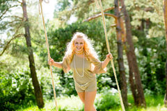 Όμορφη ξανθή γυναίκα που ταλαντεύεται στην ταλάντευση σχοινιών Στοκ Εικόνα