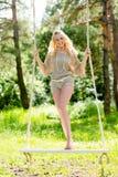 Όμορφη ξανθή γυναίκα που ταλαντεύεται στην ταλάντευση σχοινιών Στοκ φωτογραφίες με δικαίωμα ελεύθερης χρήσης