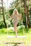 Όμορφη ξανθή γυναίκα που ταλαντεύεται στην ταλάντευση σχοινιών Στοκ Εικόνες