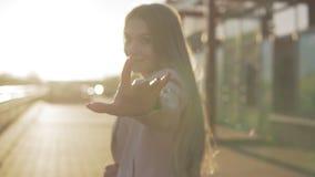 Όμορφη ξανθή γυναίκα που χαμογελά στη κάμερα και που γυρίζει γύρω στο ηλιοβασίλεμα απόθεμα βίντεο