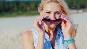 Όμορφη ξανθή γυναίκα που χαμογελά στη κάμερα, τοποθέτηση Καλοκαίρι στην παραλία απόθεμα βίντεο