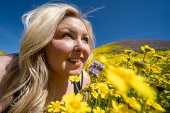 Όμορφη ξανθή γυναίκα σε έναν κίτρινο τομέα wildflower, που εξετάζει επάνω έναν μπλε ουρανό την άνοιξη Λήφθείτε Carrizo στο σαφές  στοκ εικόνες