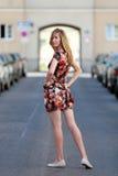 Όμορφη ξανθή γυναίκα σε ένα ζωηρόχρωμο θερινό φόρεμα στοκ εικόνες