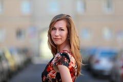 Όμορφη ξανθή γυναίκα σε ένα ζωηρόχρωμο θερινό φόρεμα Στοκ Φωτογραφίες