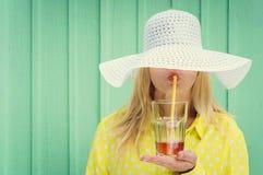 Όμορφη ξανθή γυναίκα σε μια άσπρη λεμονάδα κατανάλωσης καπέλων Στοκ εικόνα με δικαίωμα ελεύθερης χρήσης
