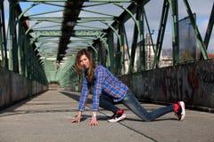 Όμορφη ξανθή γυναίκα σε μια γέφυρα με τα γκράφιτι Στοκ Εικόνες