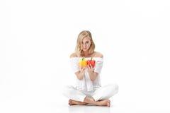 Όμορφη ξανθή γυναίκα στην άσπρη μπλούζα που κρατά το κίτρινο και κόκκινο πιπέρι κουδουνιών Υγιεινή διατροφή και διατροφή Στοκ εικόνες με δικαίωμα ελεύθερης χρήσης