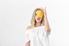 Όμορφη ξανθή γυναίκα στην άσπρη μπλούζα που κρατά το κίτρινο πιπέρι κουδουνιών υγεία σιτηρεσίου Στοκ φωτογραφία με δικαίωμα ελεύθερης χρήσης