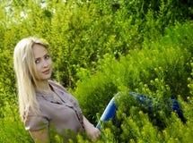 Όμορφη ξανθή γυναίκα στην πράσινη χλόη Στοκ Εικόνες