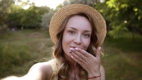 Όμορφη ξανθή γυναίκα στο καπέλο αχύρου που κάνει selfie, θέτοντας για τη κάμερα, που στέλνει το φιλί αέρα Ηλιόλουστο λιβάδι στο υ απόθεμα βίντεο