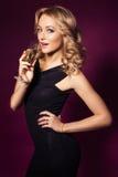 Όμορφη ξανθή γυναίκα στο μαύρο φόρεμα πολυτέλειας και το σγουρό hairstyle Στοκ φωτογραφία με δικαίωμα ελεύθερης χρήσης
